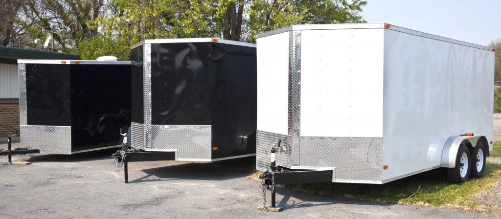 three black and white transport trailers in a row